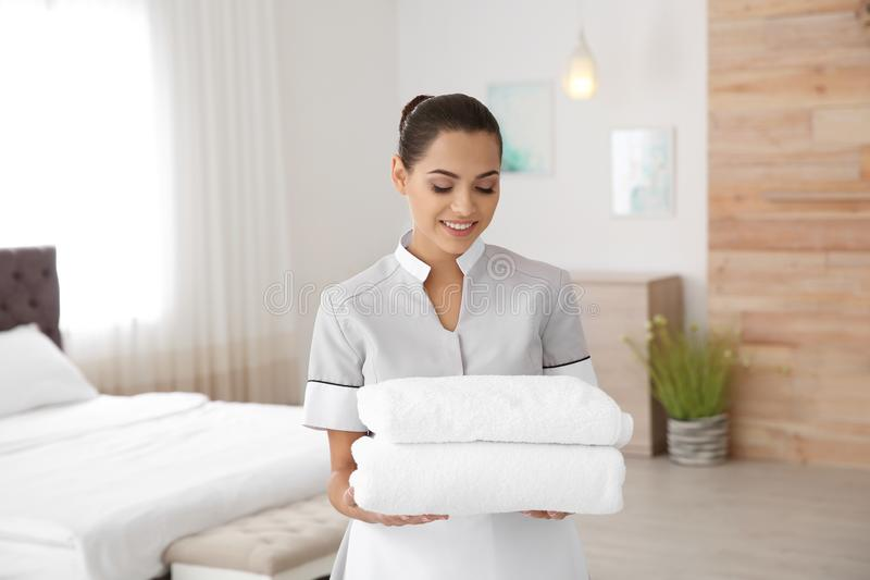 Young chambermaid with clean towels stock images