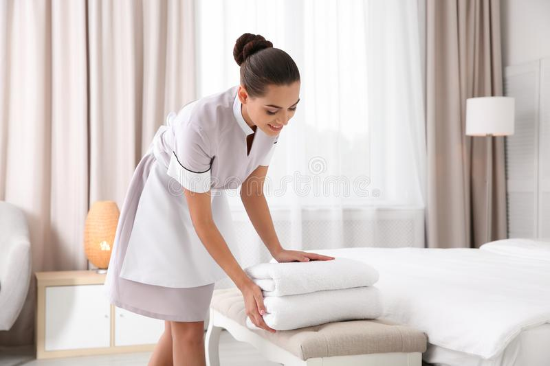 Young chambermaid putting clean towels on bed bench royalty free stock photography
