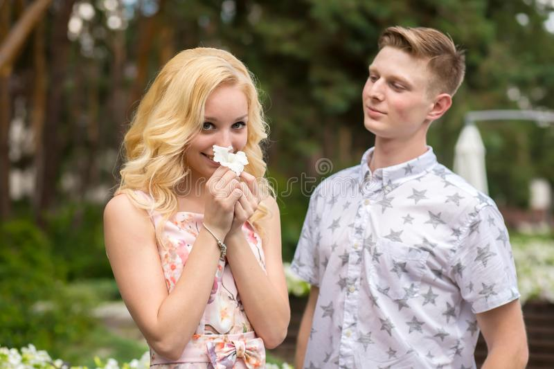 Young charming blonde girl is flirting and with a guy in the garden. Lovestory of a couple in love royalty free stock image