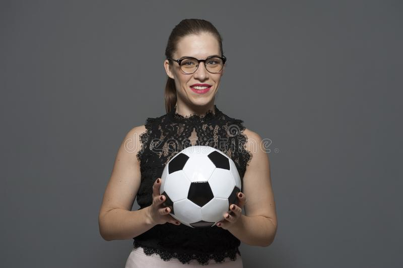Young charming businesswoman - football fan holding soccer ball royalty free stock images