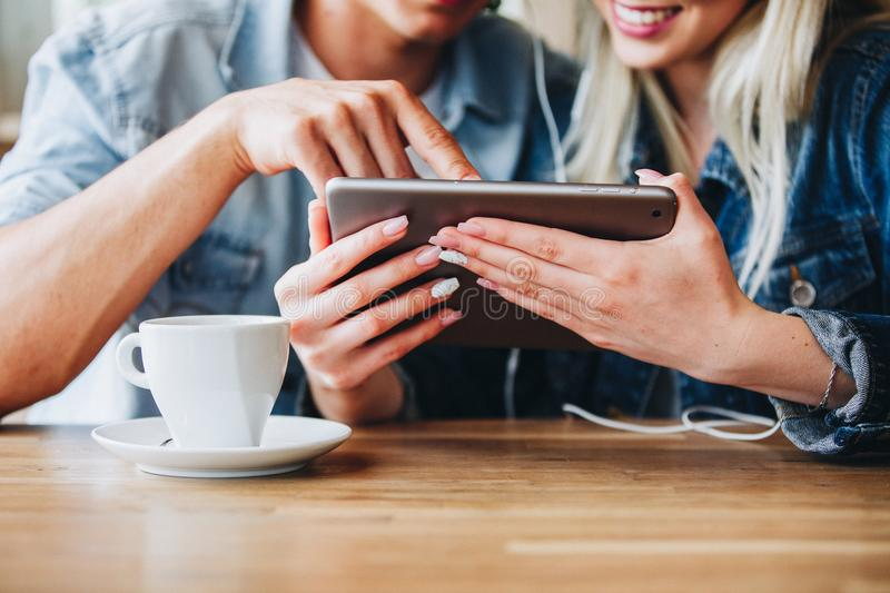 Young Charming Couple Using Tablet While Sitting Together And Dr royalty free stock photo