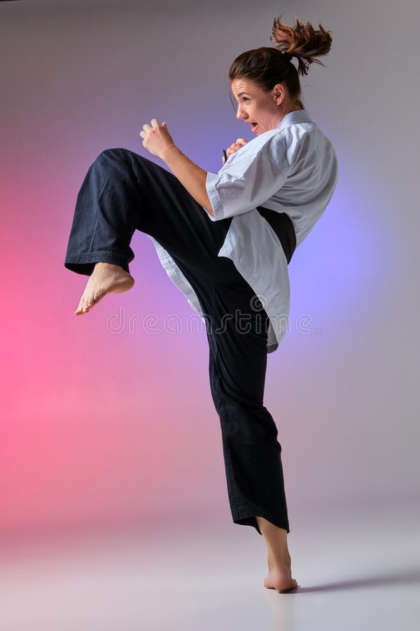 Athletic woman in traditional kimono is practicing karate in studio. Young charming female with ponytail hair, dressed in a traditional kimono is practicing royalty free stock photo