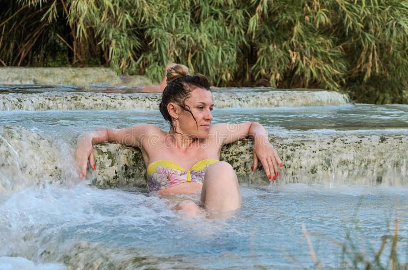 Young charming girl bathes in the healing thermal mineral springs in the resort of Saturnia Italy royalty free stock image