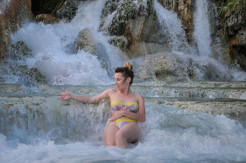 Young charming girl bathes in the healing thermal mineral springs in the resort of Saturnia Italy stock images