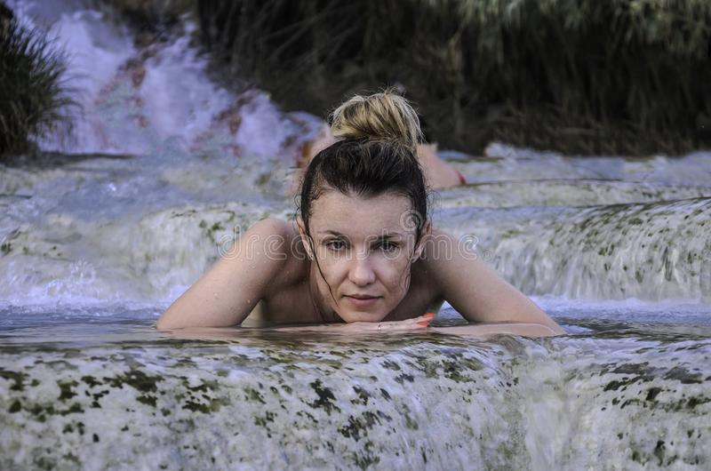 Young charming girl bathes in the healing thermal mineral springs in the resort of Saturnia Italy royalty free stock photos