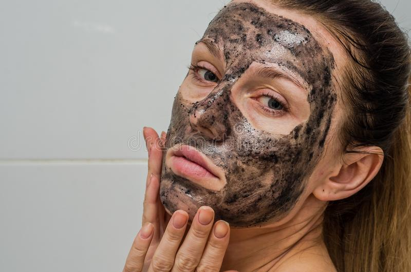 Young charming girl makes a black charcoal mask on her face stock photos