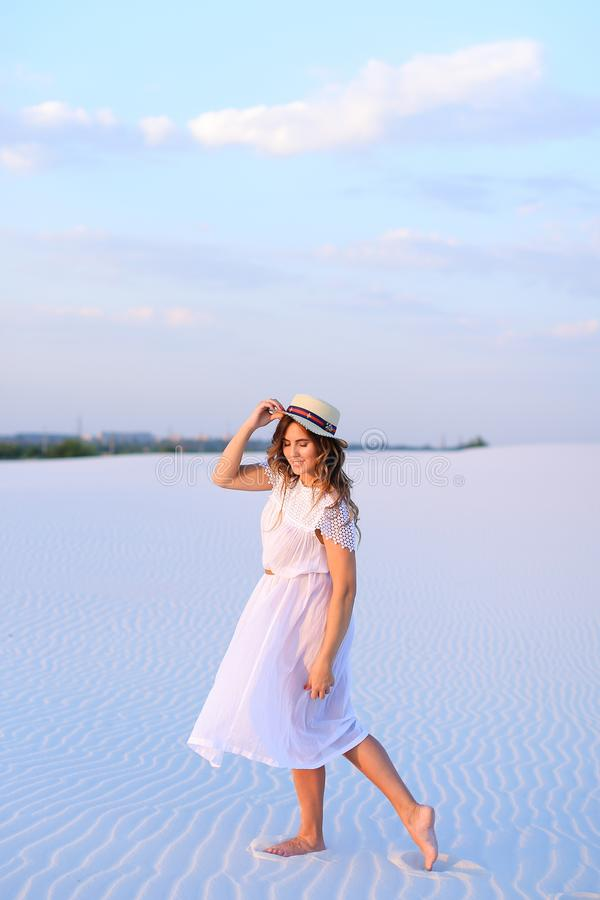 Young charming girl in white dress and hat going on sand barefoo royalty free stock image