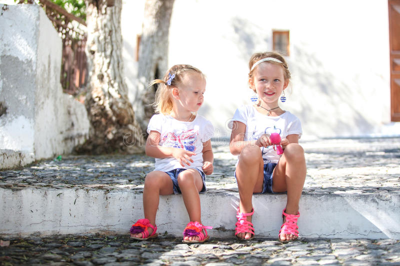 Young charming girls walk the old Greek village of stock photos