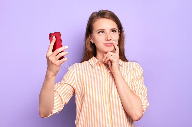 Young charming lady standing with smartphone, looking dreamy stock image