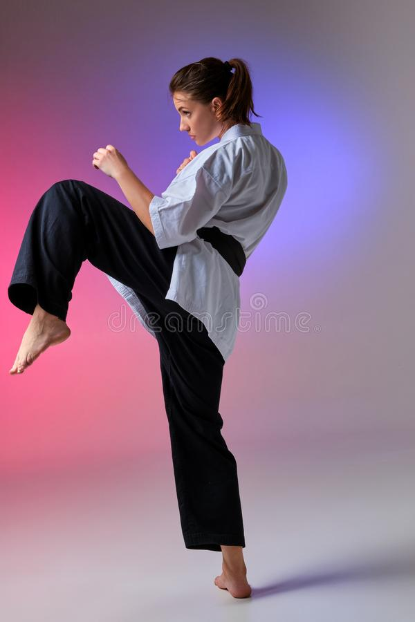Athletic woman in traditional kimono is practicing karate in studio. Young charming maiden with ponytail hair, dressed in a traditional kimono is practicing royalty free stock photography