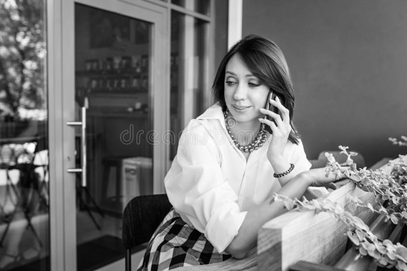 Young charming woman calling with cell telephone while sitting alone in coffee shop during free time. Attractive female with cute stock images