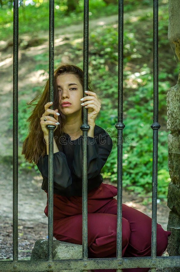 Young charming woman with long hair offender, sits behind bars in the old stone jail prisoner and looks pityingly through steel ba stock photography