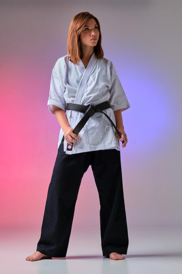 Athletic woman in traditional kimono is practicing karate in studio. Young charming woman with loose hair, dressed in a traditional kimono is looking away and stock photo