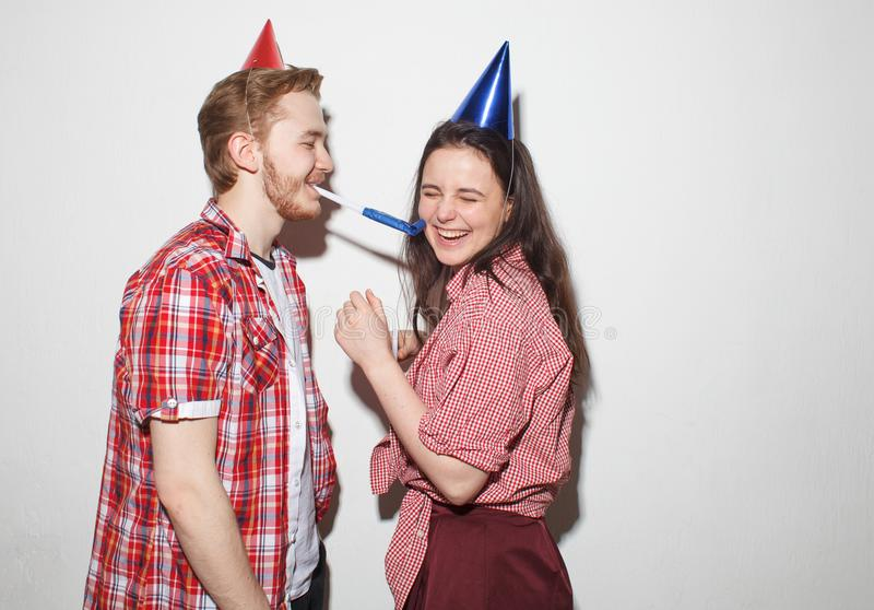 Cocky guy and girl have fun on party. Young cheeky guy and girl have fun, laughing in party caps with pipes, isolated over white stock photo