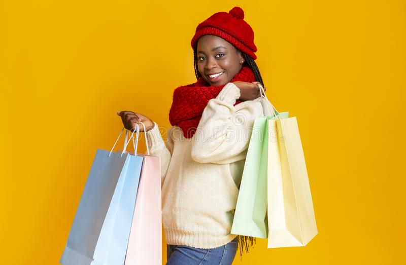 Young cheerful black woman with shopping bags over yellow background royalty free stock photos