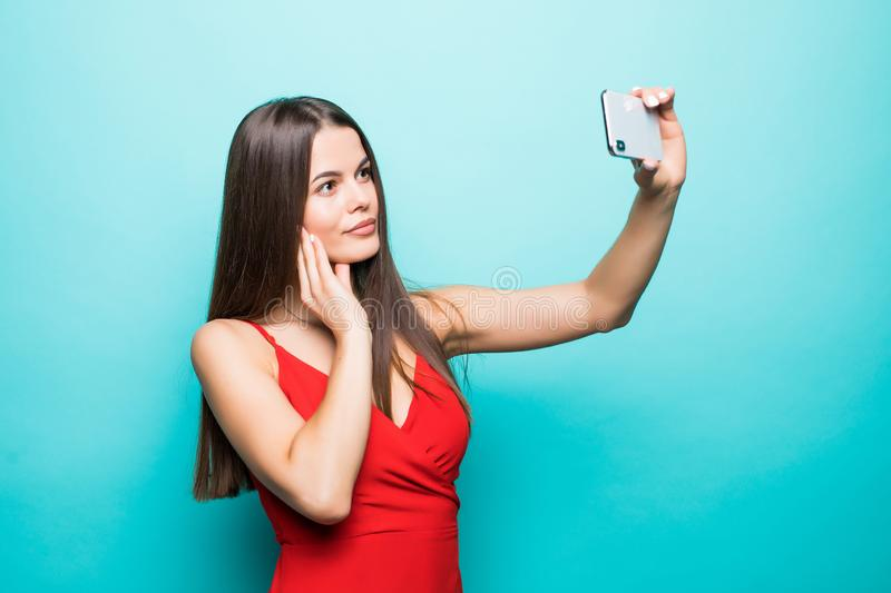 Young cheerful attractive brunette taking selfie on the camera of her phone is smiling on the blue background. Young cheerful attractive brunette is smiling on stock photos