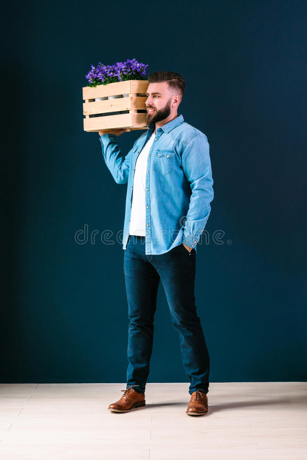 Young cheerful, bearded, hipster man, dressed in denim shirt, stands indoors, holding wooden box royalty free stock photo