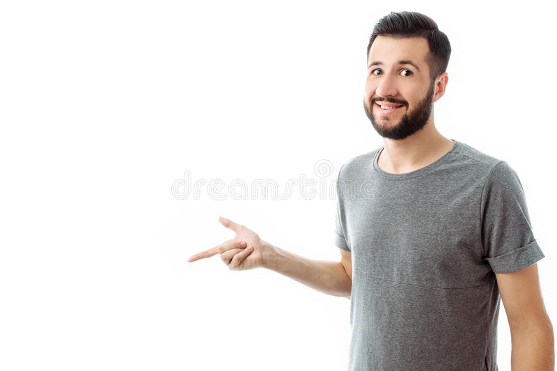 Young cheerful bearded man pointing finger at empty space on background isolated on white background stock photo