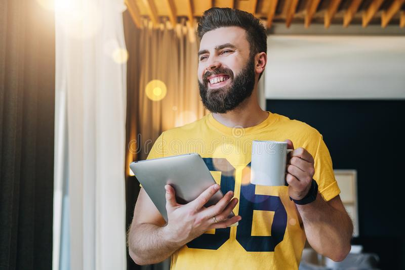 Young bearded man stands in room and holding tablet computer while drinking coffee. Guy freelancer working at home. royalty free stock photos