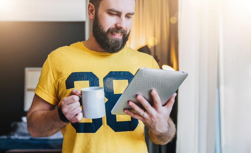 Cheerful bearded man stands and using tablet computer. Guy laughs looking screen of digital tablet while drinking coffee stock photo