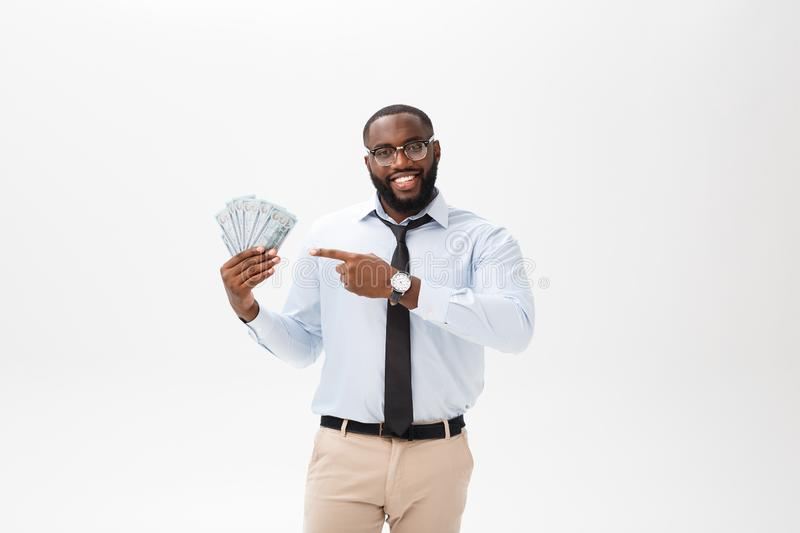 Young cheerful black businessman holding and pointing at money isolated on white royalty free stock photography
