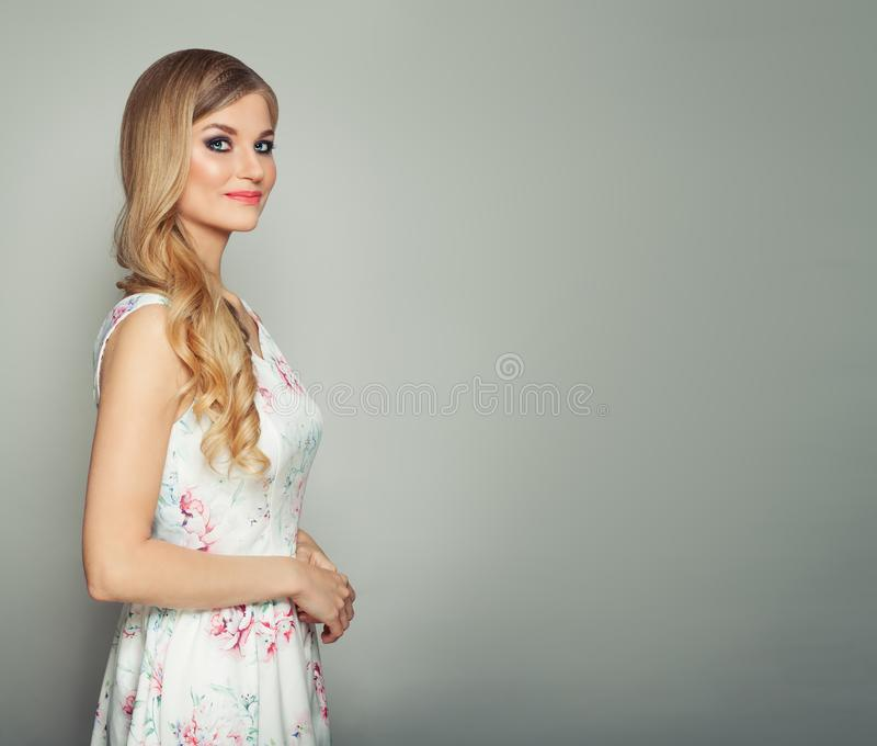Young cheerful blonde woman with curly hair and makeup smiling on background with copy space.  royalty free stock photo