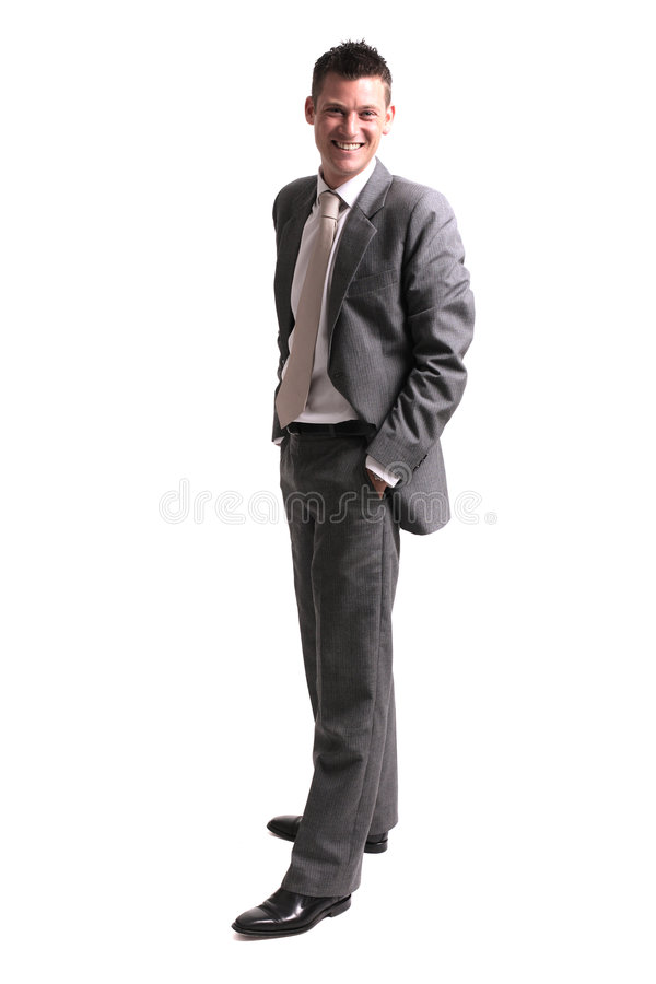 Young cheerful business man. Young satisfied smiling businessman standing over white stock image