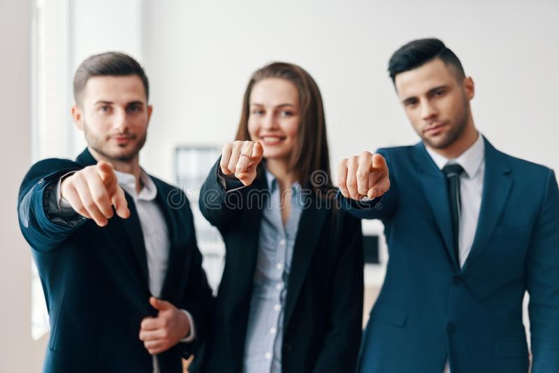 Young cheerful business people points finger at you stock photo