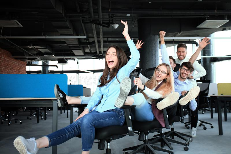 Young cheerful business people in smart casual wear having fun while racing on office chairs and smiling. royalty free stock images