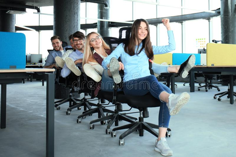 Young cheerful business people in smart casual wear having fun while racing on office chairs and smiling. royalty free stock photos