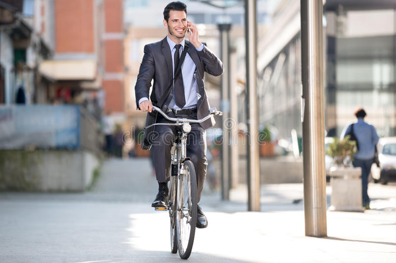 Young cheerful businessman riding a bicycle and using phone. Go to work stock photo