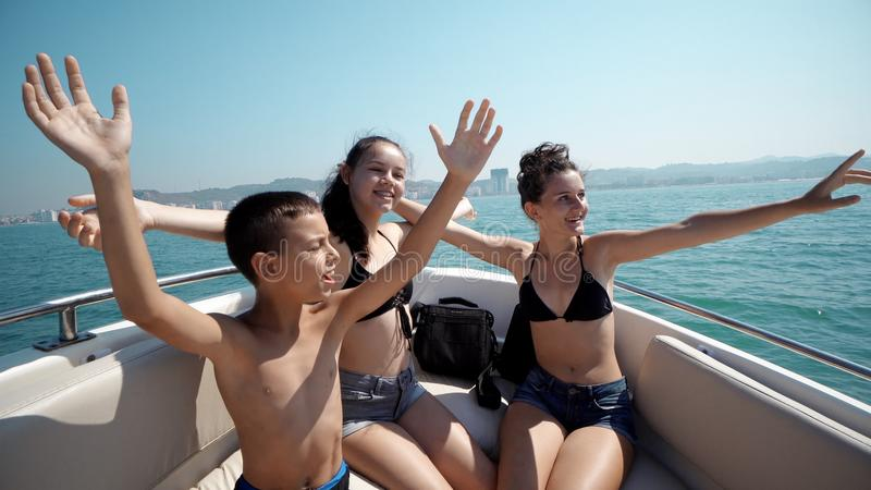 Young cheerful children having fun in boat party dancing with music on cruise trip. SLOW MOTION royalty free stock photography