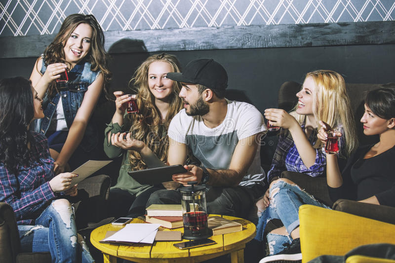 Young cheerful company of friends with mobile, tablet and tea co royalty free stock image