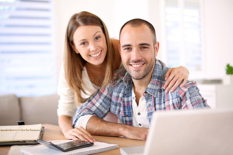 Young cheerful couple calculating budget royalty free stock photo