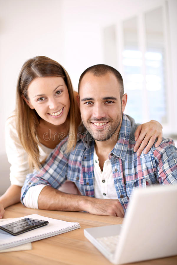 Young cheerful couple calculating savings stock photo