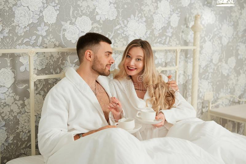 Young and cheerful couple having a breakfast drinking coffee while sitting together on the bed at home royalty free stock images