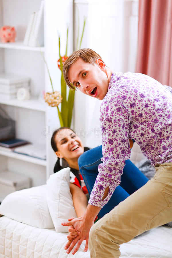 Young cheerful couple having fun at home stock photo