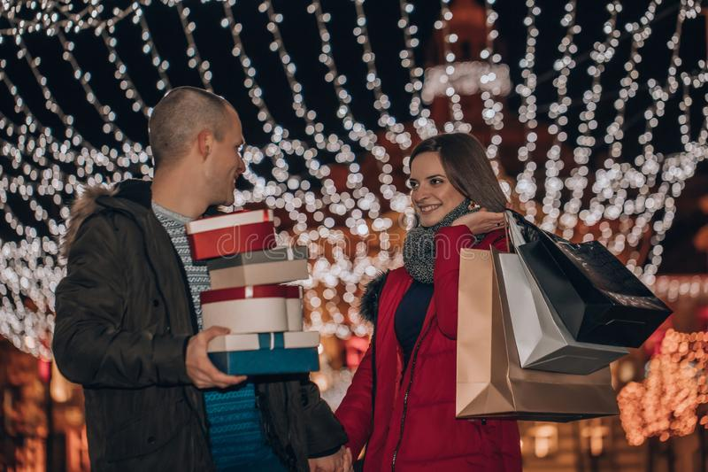 Young couple holding presents in a box and bags at night stock images