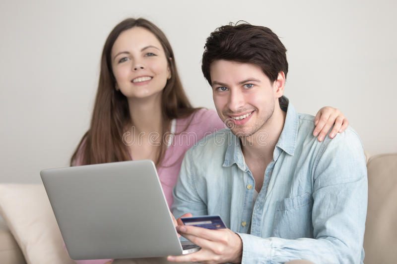 Young cheerful couple shopping online via laptop with credit ca stock photo
