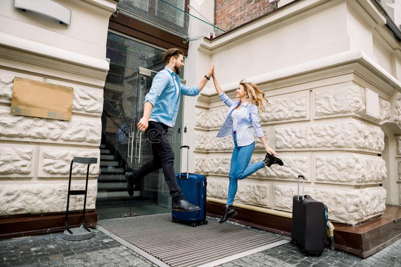 Young cheerful couple with suitcases jumping and giving five, having fun, before arriving to the hotel. Couple having stock photos