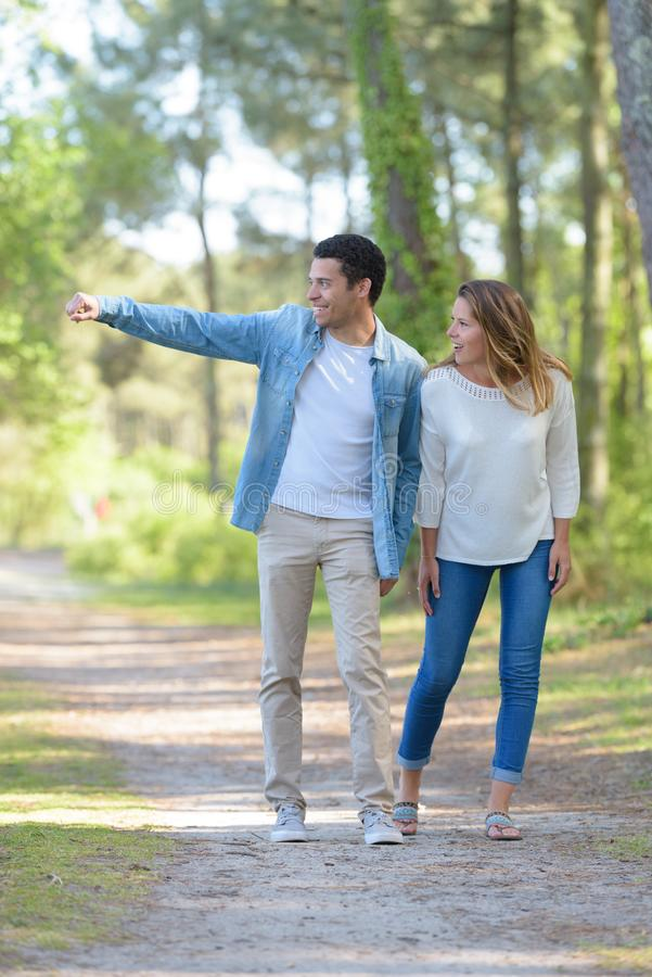 Young cheerful couple walking in park royalty free stock photography