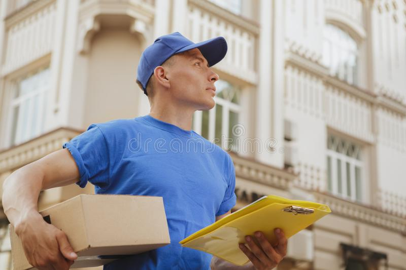 Young cheerful delivery man with parcel cardboard box on the city streets royalty free stock photography