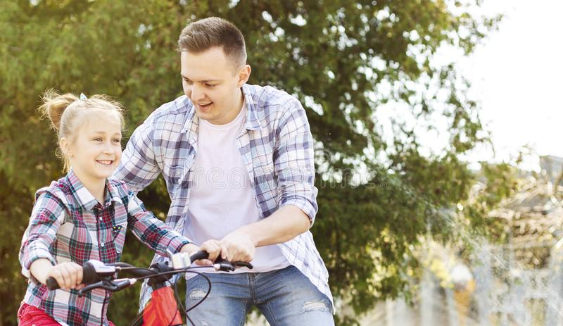 Happy girl is cycling with her father help royalty free stock images
