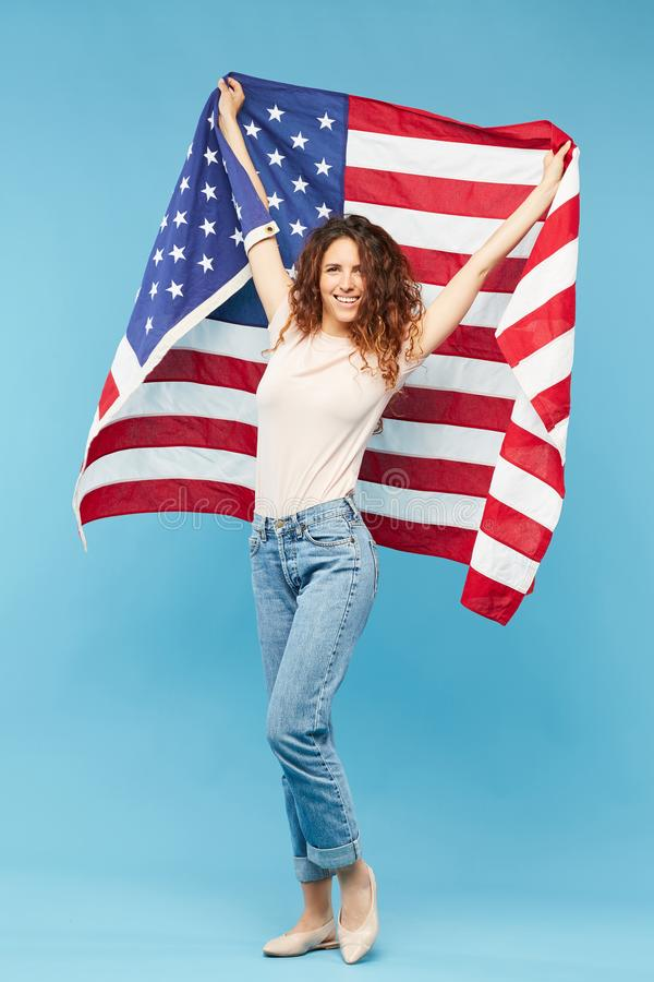 Young cheerful female with long dark curly hair holding flag of USA royalty free stock photos