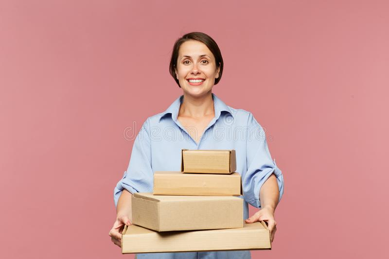 Young cheerful female online shopper with stack of packed orders stock photography