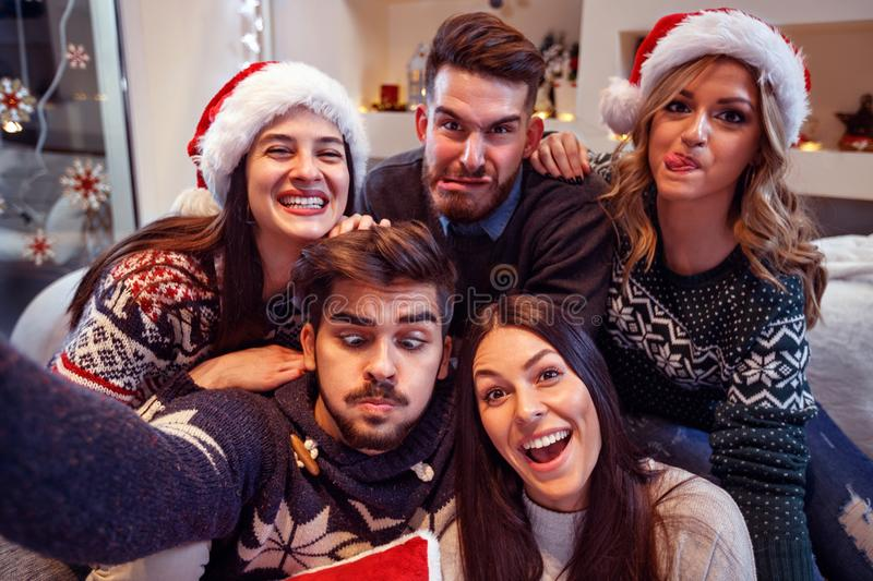 Cheerful friends make funny face in New Year`s eve stock photo