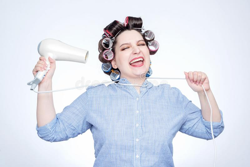 Young cheerful girl with curlers choking herself with a cord from a hairdryer. Sick of all royalty free stock image