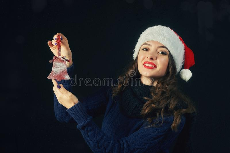 Young cheerful girl in Santa hat on dark background royalty free stock photography