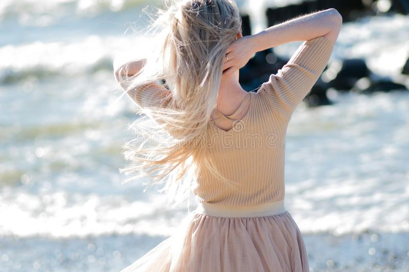 Young cheerful girl on the seashore. Young blonde woman smiling. Open arms hugs the ocean royalty free stock photography