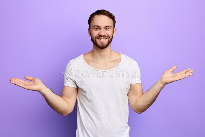 Young cheerful happy handsome guy raising his hands with open palms royalty free stock photos